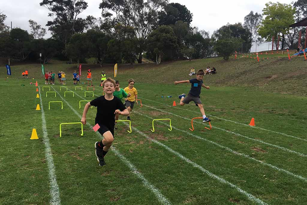 Sports day, students running over hurdles.